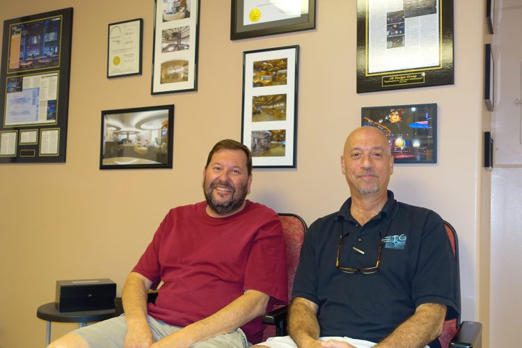 Jay Winters (left) and Edward Kaye in front of a few of their mementoes at the JK Design Group offices.